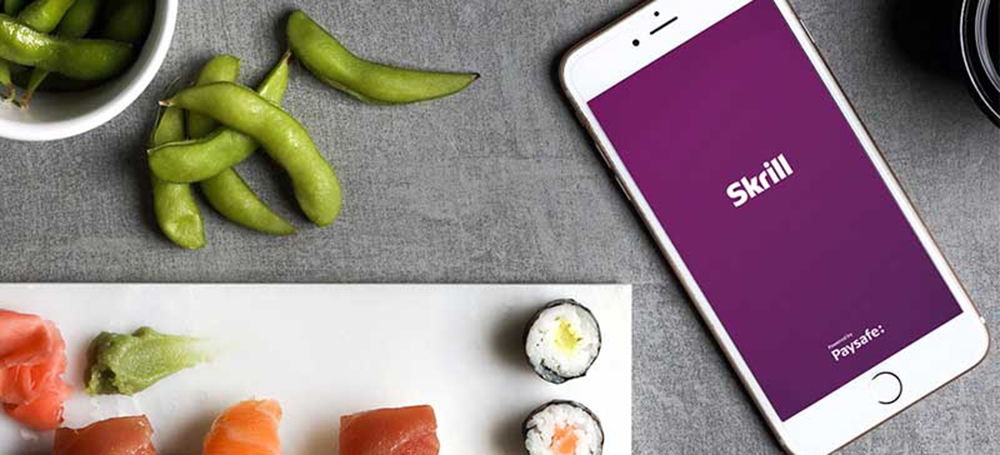 mobile phone with open Skrill app next to sushi set