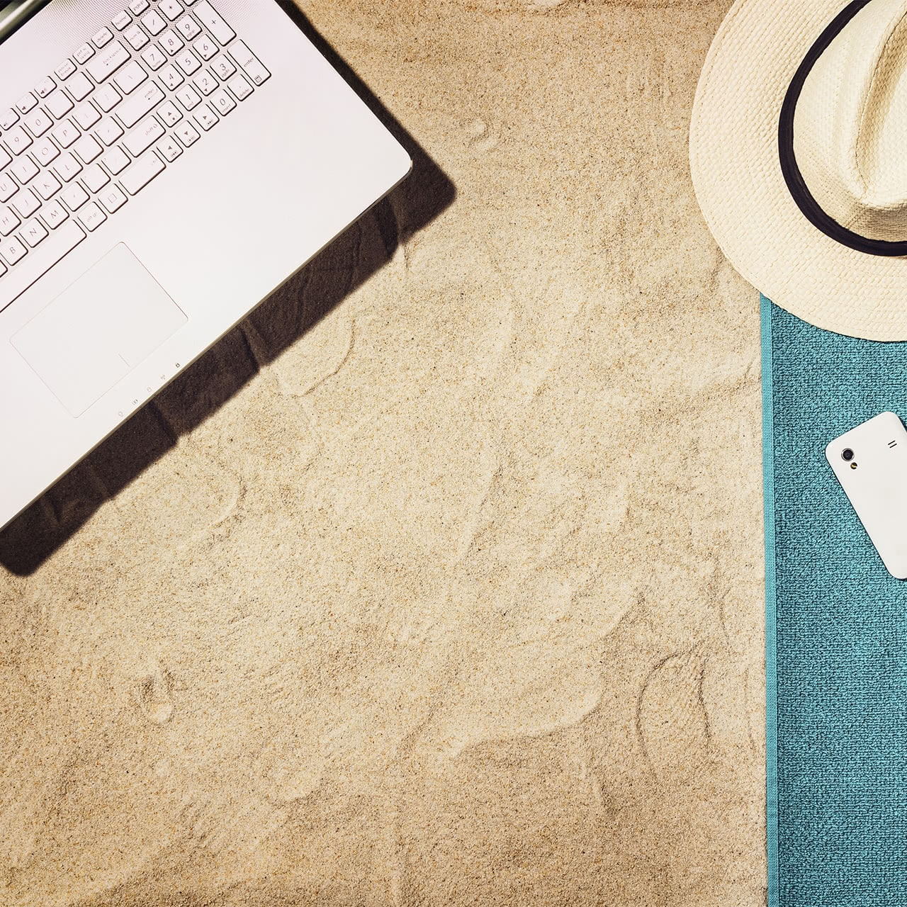 laptop on sand and summer hat on towel