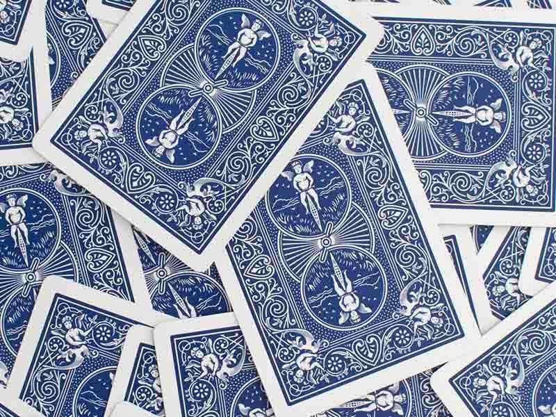 Pile of blue playings cards scattered on a surface