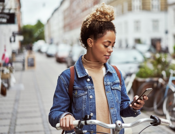 Young beautiful lady on a bike, stopped in the middle of the street and looking at her phone